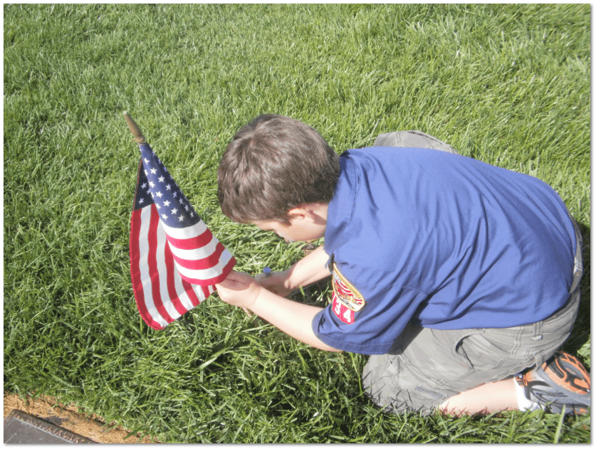 Boy Scout placing U.S. flag on a veteran's grave at Riverside National Cemetery