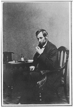 photo of American President Abraham Lincoln seated at a small table