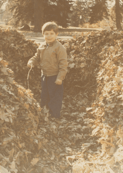 photo taken by Scott Phillips of his son in a leaf fort, circa 1979