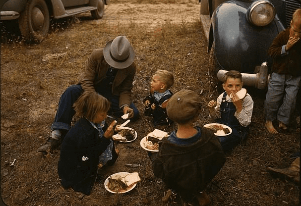 photo of a homesteader and his children eating barbeque at the Pie Town, New Mexico, fair c.1940
