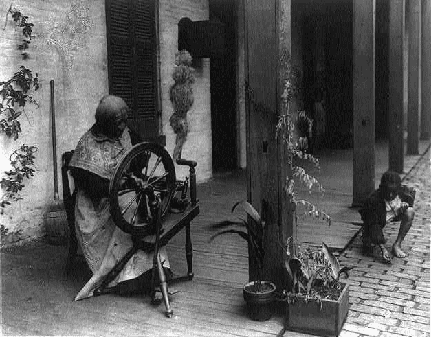 photo of a woman using a spinning wheel c.1907
