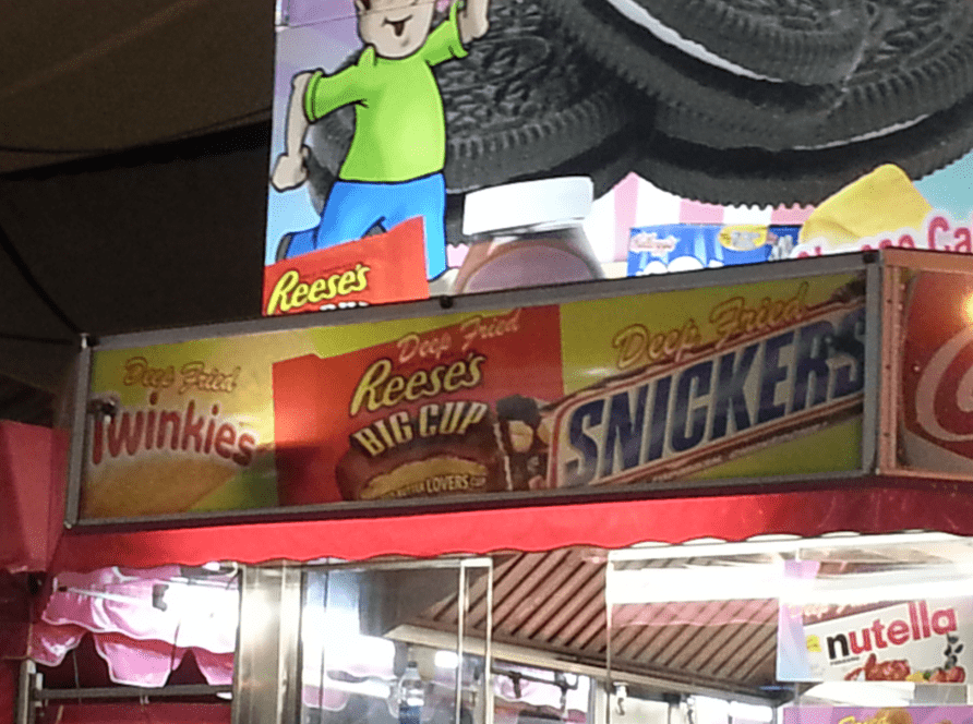 photo of a booth offering deep fried Twinkies, Reese's Peanut Butter Cups, and Snickers at the California State Fair