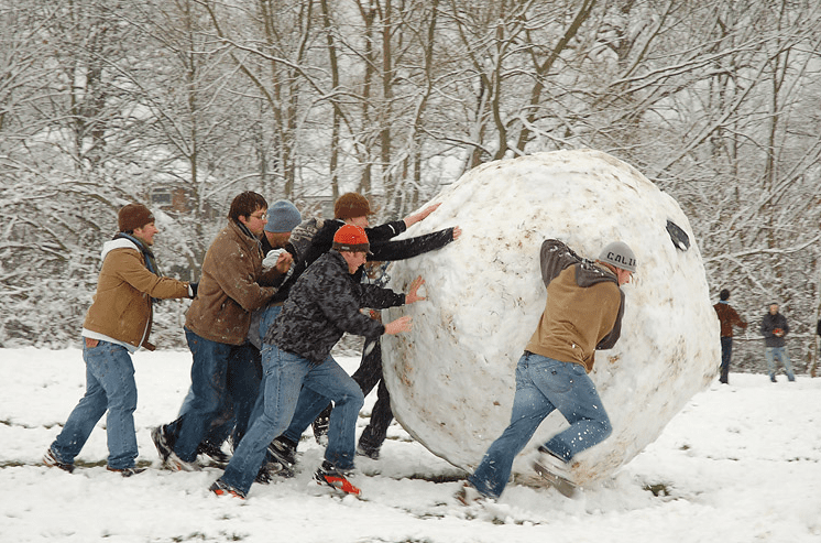 photo of some boys making a giant snowball