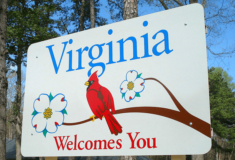 photo of a Virginia state welcome sign featuring the state bird (cardinal) and state tree and flower (dogwood)