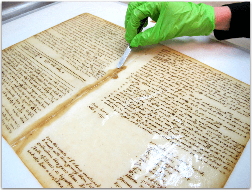 photo of the Bradford Manuscript being restored by the Northeast Document Conservation Center (NEDCC)