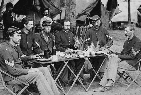Photo: Noncommissioned Officers Mess of Company D, 93d New York Infantry, Bealeton, Virginia, Aug. 1863. Source: Wikipedia.