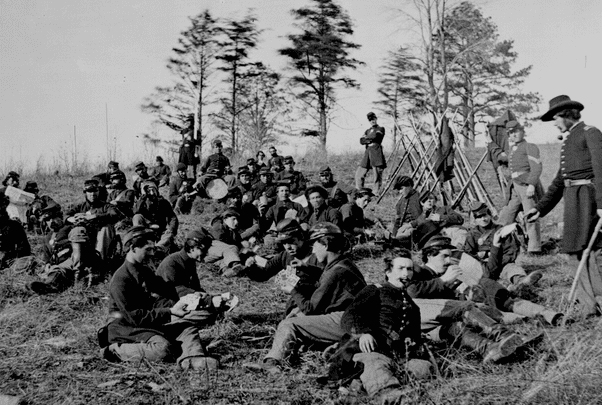 Photo: Soldiers at rest after drill, Petersburg, Va., 1864. The soldiers are seated reading letters and papers and playing cards. Credit: National Archives.