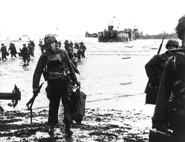Photo: carrying full equipment, American assault troops move onto Utah Beach on the northern coast of France, 6 June 1944