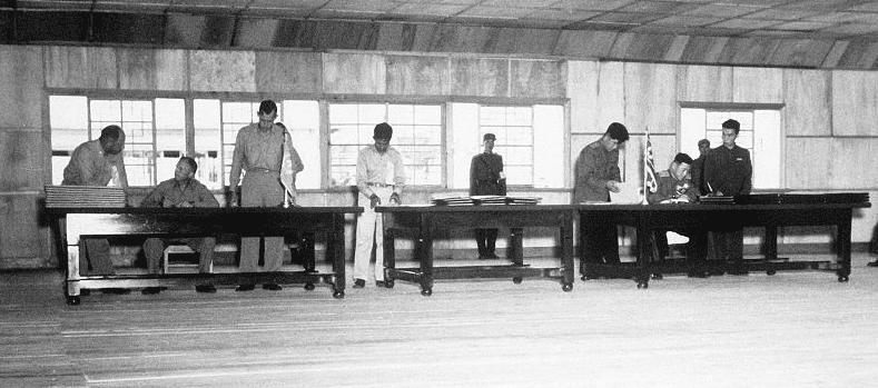 Photo: UN delegate Lieut. Gen. William K. Harrison, Jr. (seated left), and Korean People's Army and Chinese People's Volunteers delegate Gen. Nam Il (seated right) signing the Korean War armistice agreement at P'anmunj?m, Korea, 27 July 1953