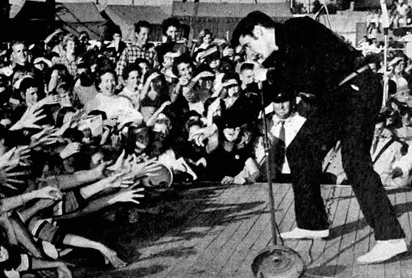 Photo: Elvis Presley performing live at the Mississippi-Alabama Fairgrounds in Tupelo, Mississippi, 26 September 1956. Credit: Wikimedia Commons.