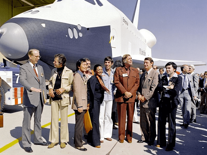 """Photo: the Shuttle Enterprise rolls out of the Palmdale manufacturing facilities with Star Trek television cast members. From left to right they are: Dr. James C. Fletcher (NASA Administrator), DeForest Kelley (Dr. """"Bones"""" McCoy), George Takei (Mr. Sulu), James Doohan (Chief Engineer Montgomery """"Scotty"""" Scott), Nichelle Nichols (Lt. Uhura), Leonard Nimoy (Mr. Spock), Gene Roddenberry (Star Trek creator), an unnamed official (probably from NASA), and Walter Koenig (Ensign Pavel Chekov)."""