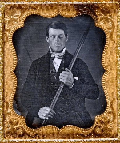 Photo: studio portrait of brain-injury survivor Phineas P. Gage (1823-1860) shown holding the tamping iron which injured him