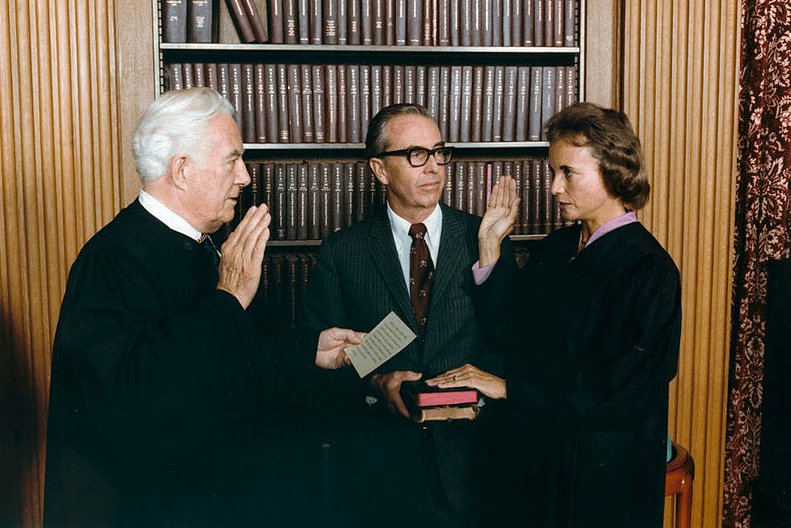 Photo: Sandra Day O'Connor being sworn in as a Supreme Court Justice by Chief Justice Warren Burger. Her husband John O'Connor looks on, 25 September 1981. Credit: U.S. National Archives; Wikimedia Commons.