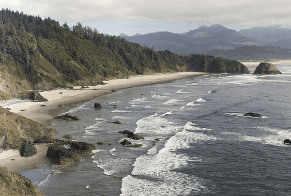 Photo: the Oregon coastline looking south from Ecola State Park, with Haystack Rock in the distance. Credit: Cacophony; Wikimedia Commons.