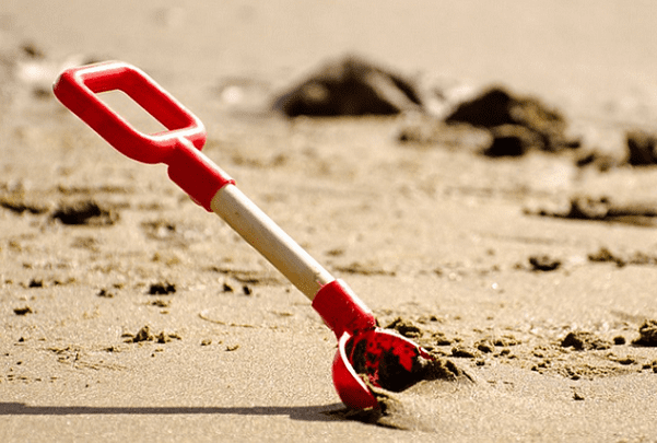 Photo: a shovel digging into the sand on a beach
