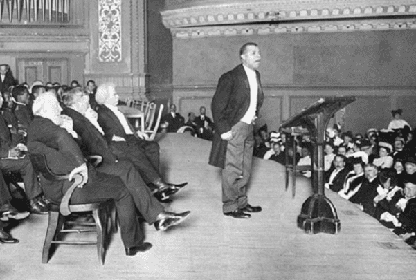 Photo: Booker T. Washington speaking to a Carnegie Hall audience during his Tuskegee Institute Silver Anniversary lecture, 1906. Note that Mark Twain is seated just behind Mr. Washington. Credit: New York Times; Wikimedia Commons.