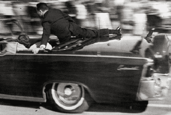 Photo: Secret Service agent Clinton Hill shielding the occupants of President Kennedy's limousine: President Kennedy, Jackie Kennedy, Texas Governor John Connally, and his wife Nellie, 22 November 1963. Credit: Justin Newman; Wikimedia Commons.