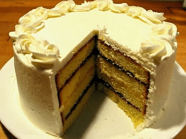 Photo: a layered pound cake, with alternating interstitial spaces filled with raspberry jam and lemon curd, finished with buttercream frosting. Credit: Scheinwerfermann; Wikimedia Commons.