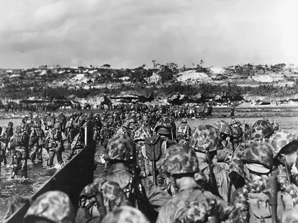 Photo: U.S. Marine reinforcements wade ashore to support the beachhead on Okinawa, 1 April 1945. Credit: National Archives; Wikimedia Commons.