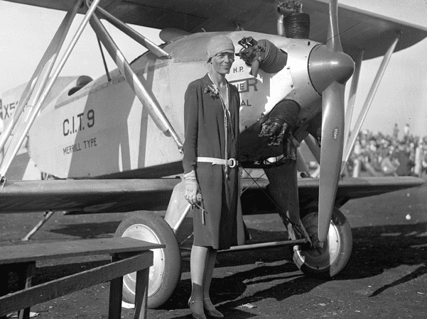Photo: Amelia Earhart, wearing a dress, standing beside a Merrill CIT-9 Safety Plane, c. 1928. Credit: UCLA Library; Wikimedia Commons.
