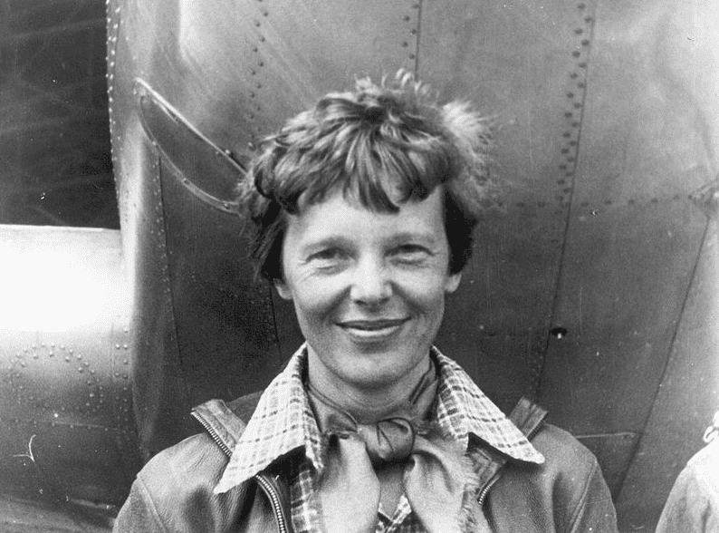 Photo: Amelia Earhart standing under nose of her Lockheed Model 10-E Electra – the plane she was flying when she mysteriously disappeared