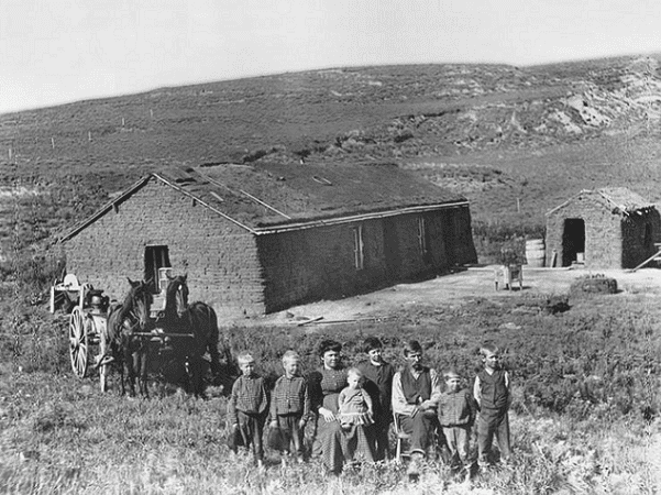 Photo: a farm family poses outside their sod house in eastern Custer County, Nebraska, ca. 1888. Courtesy Nebraska State Historical Society. Credit: U.S. Department of Agriculture; Wikimedia Commons.