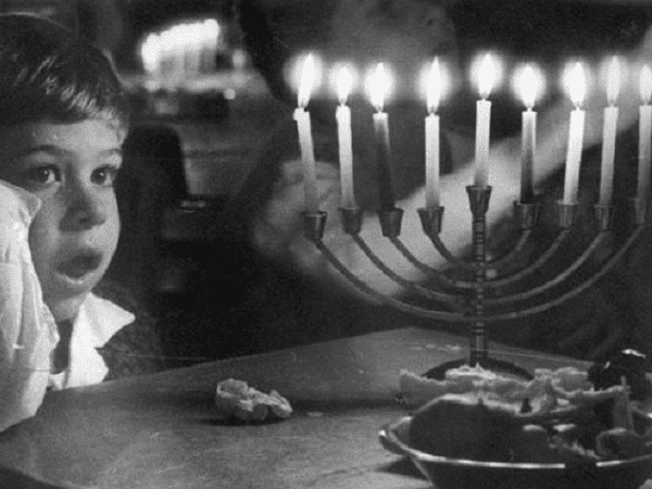 Photo: boy in front of a menorah, c. 1955. Credit: PikiWiki - Israel free image collection project; Wikimedia Commons.