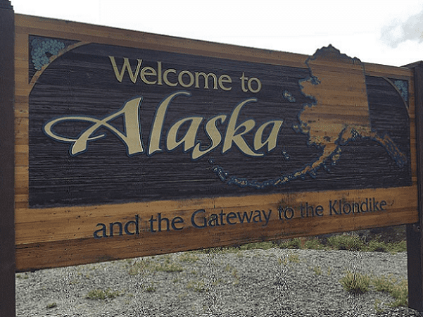 Photo: Alaska welcome sign on the Klondike Highway. Credit: Wikimedia Commons.