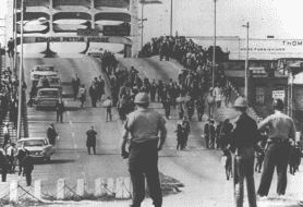 Photo: police watch marchers turn around after crossing the Edmund Pettus Bridge on Tuesday, 9 March 1965