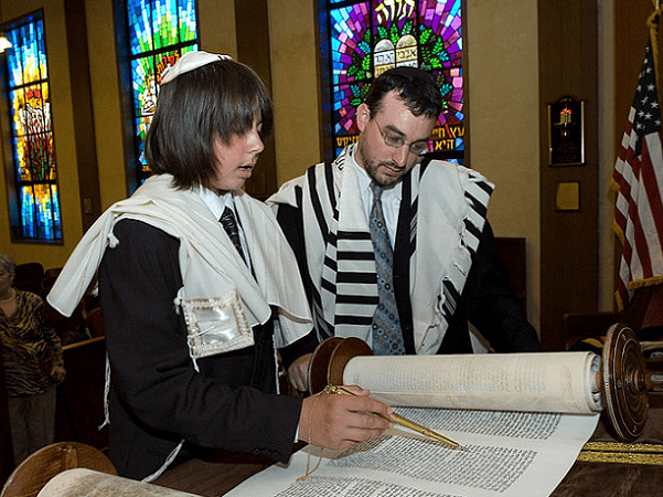 Photo: Jewish boy reading the Torah at his Bar Mitzvah, using a Yaad (A Torah pointer). Credit: Eli; Wikimedia Commons.