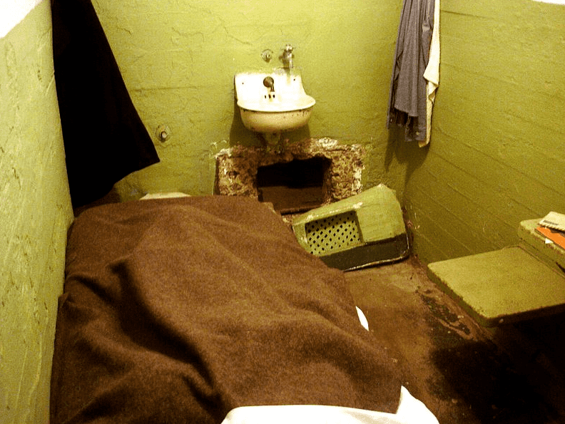 Photo: escapee's prison cell, with widened vent opening beneath the sink