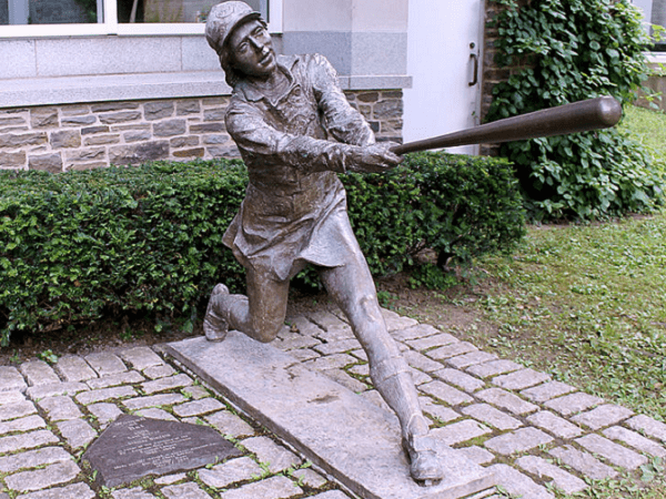 Photo: bronze sculpture at the Baseball Hall of Fame in Cooperstown, New York, which commemorates the All-American Girls Professional Baseball League. Credit: EricEnfermero; Wikimedia Commons.