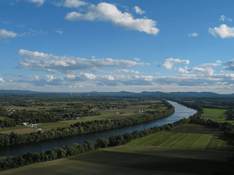 Photo: the Connecticut River and Pioneer Valley of Massachusetts. Looking south from Mt. Sugarloaf in Deerfield, toward the towns of Sunderland, Amherst and Whately