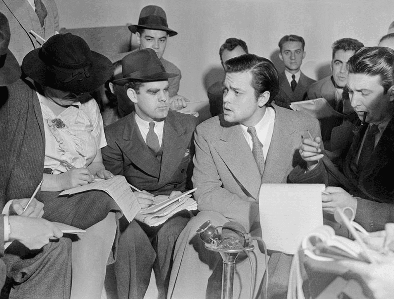 Photo: Orson Welles meeting with reporters in an effort to explain that no one connected with the War of the Worlds radio broadcast had any idea the show would cause panic, 31 October 1938