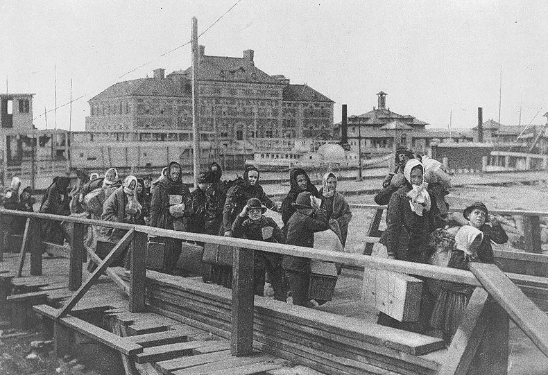 "Photo: ""Emigrants coming up the board-walk from the barge, which has taken them off the steamship company's docks, and transported them to Ellis Island. The big building in the background is the new hospital just opened,"" 1902"