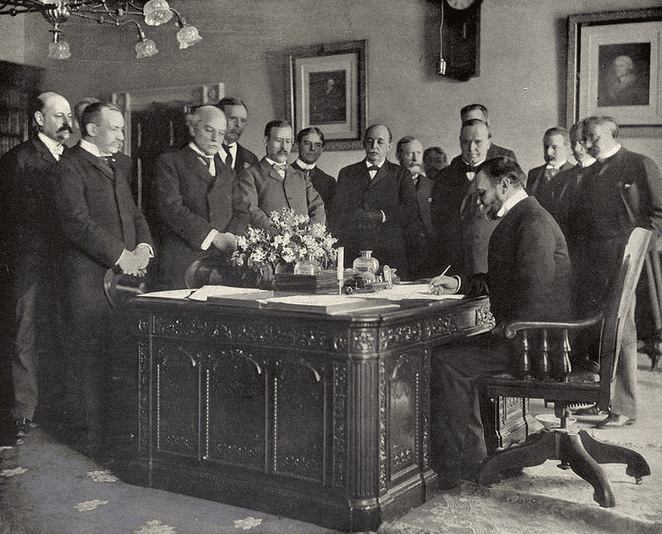Photo: John Hay, Secretary of State, signing the memorandum of ratification for the Treaty of Paris on behalf of the United States, 10 December 1898