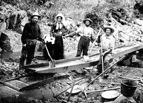 Photo: a woman with three men panning for gold during the California Gold Rush, 9 July 1850