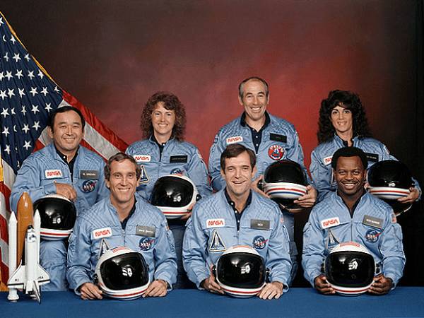 Photo: the Challenger crew. In the back row from left to right: Ellison S. Onizuka, Sharon Christa McAuliffe, Greg Jarvis, and Judy Resnik. In the front row from left to right: Michael J. Smith, Dick Scobee, and Ron McNair. Credit: NASA; Wikimedia Commons.