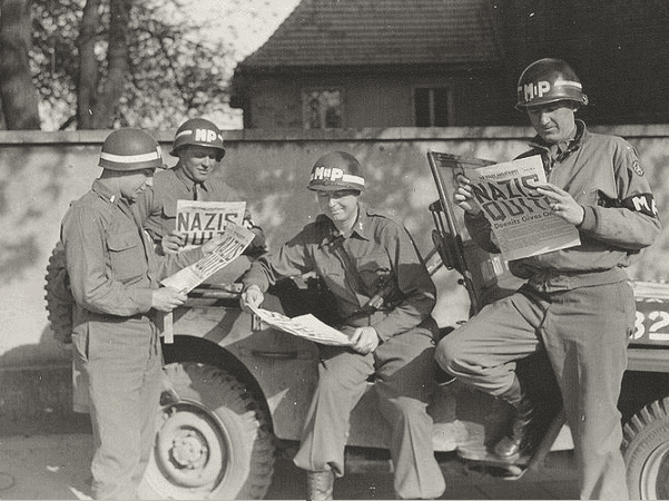 "Photo: four MPs take a break along a German road to read in the ""Stars and Stripes"" newspaper about the Nazi surrender during WWII, May 1945. Credit: U.S. Army; Wikimedia Commons."