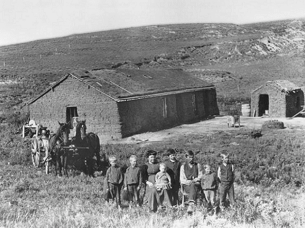 Photo: a farm family poses outside their sod house in eastern Custer County, Nebraska, c. 1888. Note the clothes made from the same bolt of cloth. Courtesy Nebraska State Historical Society. Credit: U.S. Department of Agriculture; Wikimedia Commons.