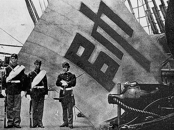 Photo: Sujagi flag, captured at Fort McKee in the attacks on the Salee River Forts, June 10 and 11, 1871, by Corporal Charles Brown of the USS Colorado (left) and Private Hugh Purvis of the USS Alaska (middle). Both were awarded the Medal of Honor. Captain McLane Tilton, USMC, (right) commanded the Marines. Photograph was taken on the USS Colorado, Captain George H. Cooper commanding, Flagship of Rear Admiral John Rodgers, commanding U.S. Asiatic Fleet. Credit: r Felice Beato; United States Marine Corps Historical Division photographic archives; Wikimedia Commons.