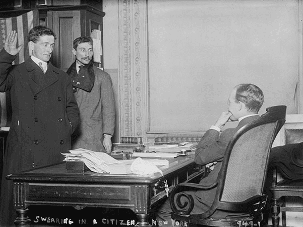 Photo: a man taking the required citizenship oath of allegiance in front of a judge in New York City (1910). Credit: Library of Congress, Prints and Photographs Division.