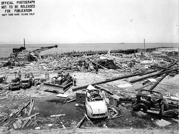 "Photo: Port Chicago after the 17 July 1944 explosion.Source states: ""This view looks north, showing the wreckage of Building A-7 (Joiner Shop) in the center and ship pier beyond... Bulldozer and damaged automobiles in the foreground, railway crane at left, and scattered pilings."" Credit: U.S. Naval Historical Center; Wikimedia Commons."