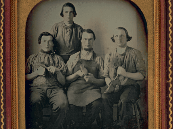 Photo: Occupational group portrait of four shoemakers, one full-length, standing, other three seated, holding shoes and shoe making equipment, c. 1840-1860. Credit: Library of Congress, Prints and Photographs Division.