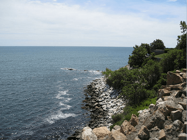 Photo: the rocky shoreline of Newport, Rhode Island, showing a clear line where high tide occurs. Narraganset Bay, which eventually empties into the Atlantic Ocean, is seen in the background. Credit: Geoking66; Wikimedia Commons.
