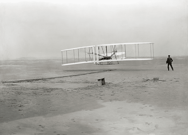 Photo: the first powered, controlled, sustained airplane flight in history. Orville Wright, age 32, is at the controls of the machine, lying prone on the lower wing with hips in the cradle which operated the wing-warping mechanism. His brother, Wilbur Wright, age 36, ran alongside to help balance the machine, having just released his hold on the forward upright of the right wing.
