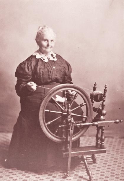 "Photo: Mrs. Chris ""Anna"" White of South Dakota at her spinning wheel"
