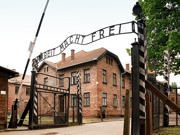 """Photo: gate to the German concentration camp, Auschwitz I (the main camp), Poland, with its Arbeit macht frei sign (""""work sets you free""""). Credit: xiquinhosilva; Wikimedia Commons."""