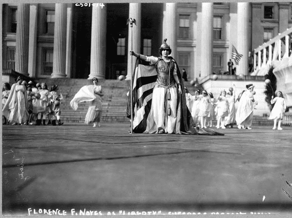 "Photo: German actress Hedwig Reicher wearing costume of ""Columbia"" with other suffrage pageant participants standing in background in front of the Treasury Building, March 3, 1913, Washington, D.C. Credit: Library of Congress, Prints and Photographs Division."