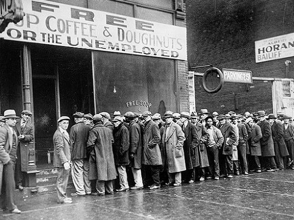 Photo: unemployed men standing in line outside a depression-era soup kitchen in Chicago, 1931. Credit: U.S. National Archives and Records Administration; Wikimedia Commons.